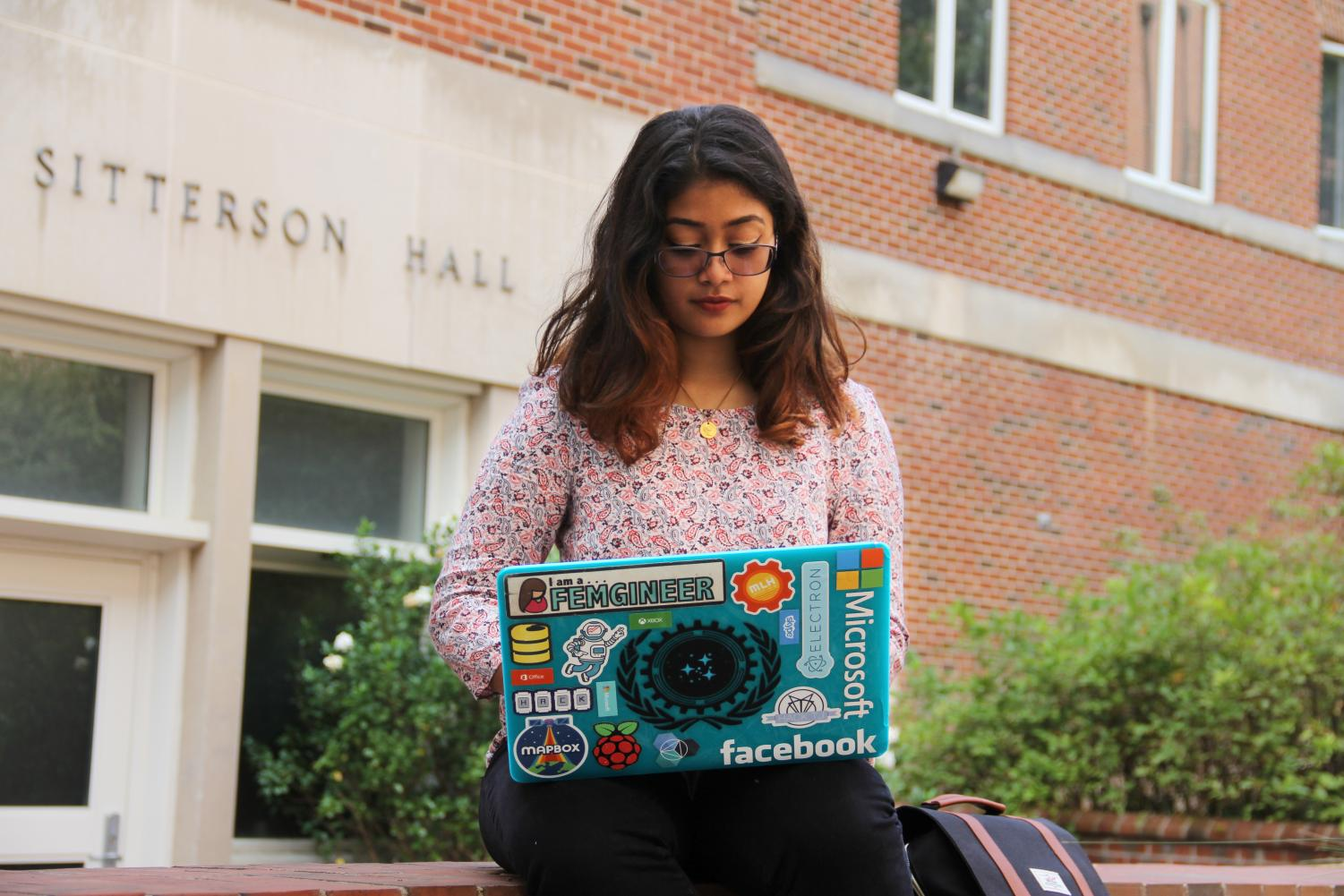 Jefferson Class of 2016 graduate, Sweta Karlekar, is working on her laptop outside of Sitterson Hall on the UNC Chapel Hill campus.