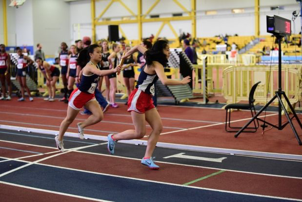 "Sophomore Tammy Ding and junior Mia Yang compete in a relay at VHSL Region 5C Indoor Championships. Whether indoor or not, Ding finds track to be a blessing. ""It's so easy to get caught up in small matters—which can easily ruin your day—but I find that track helps me relax and detoxify,"" Ding said."