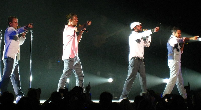 The Backstreet Boys point to the crowd at a 2008 concert. Courtesy of Anirudh Koul through Flickr, acquired through Wikimedia Commons