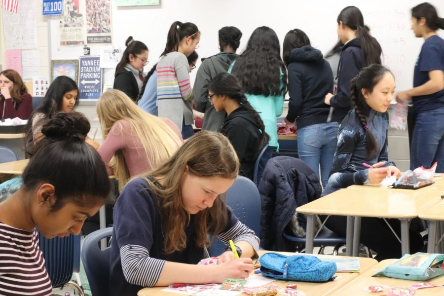 Freshmen Aafreen Ali and Rachel Lewis write notes and make goody bags in the Valentine's Day Service Activity hosted by Jefferson's UNICEF chapter. This event was hosted to help support UNICEF's monthly goal and INOVA's Children's Hospital.