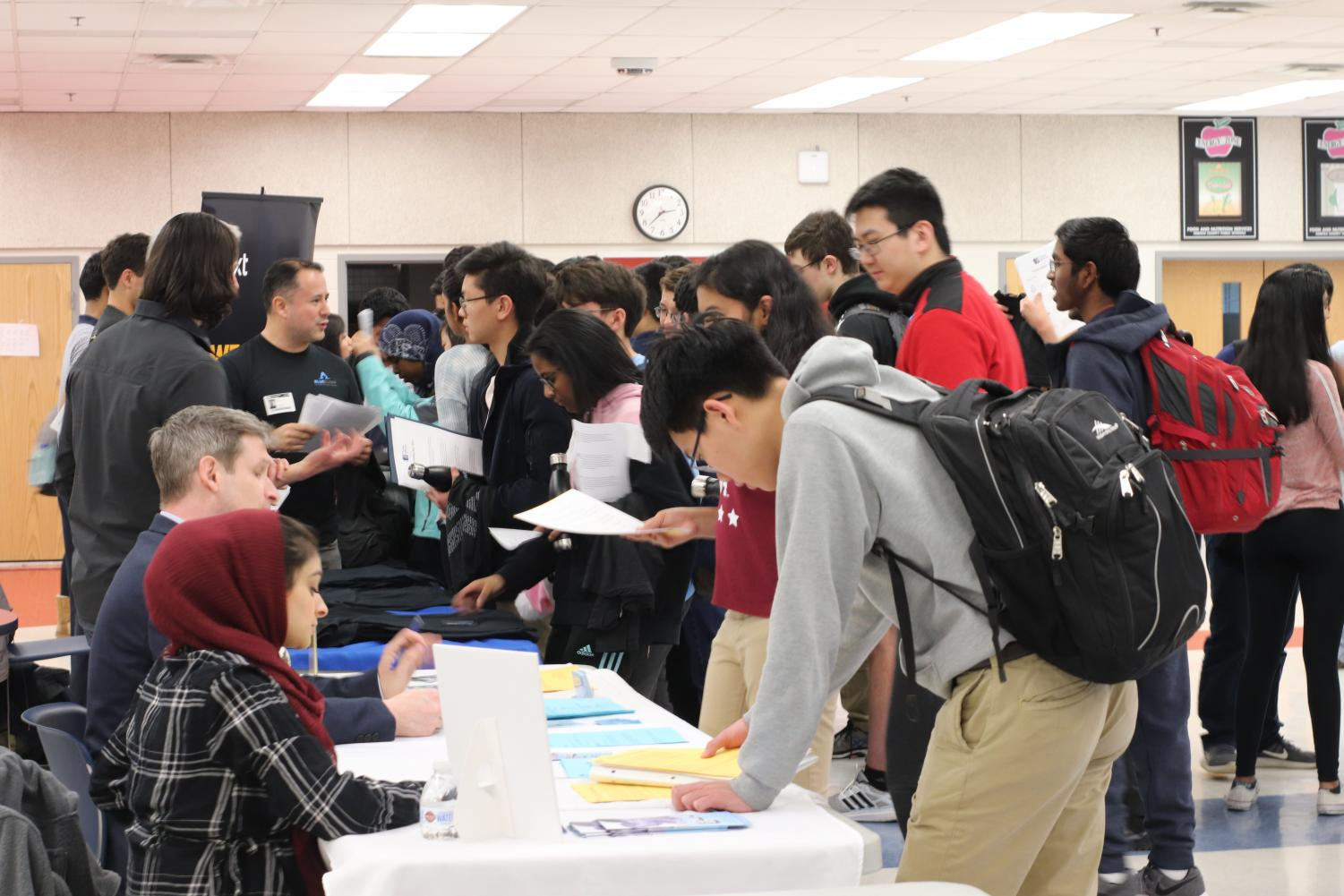 Junior Adam Yao discusses possible summer opportunities with representatives from various companies, such as Yext, during the Internship Fair. The fair is designed to aid students in finding summer opportunities to expand their knowledge and explore their career.