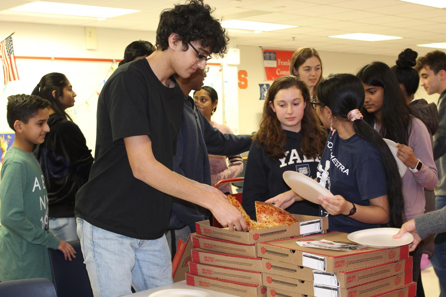 Everyone+crowds+the+pizza+boxes+with+sophomore+Raunak+Daga+grabbing+the+first+slice+of+the+event.