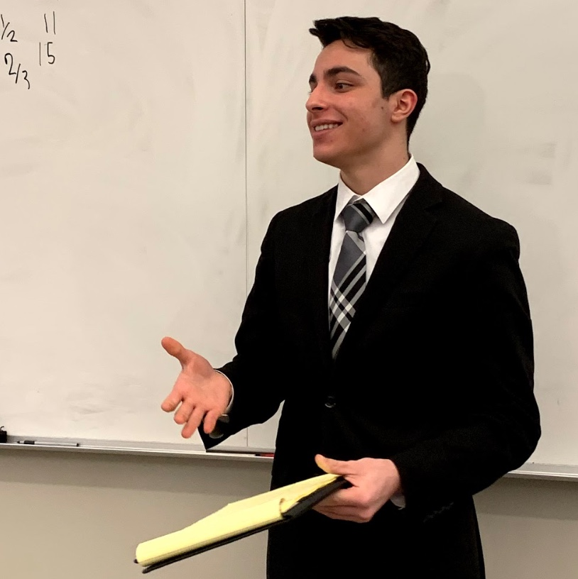 Jefferson%E2%80%99s+Congressional+Debate+captain%2C+Dany+Matar%2C+smiles+at+his+audience+as+he+finishes+his+first+speech+in+the+2018-2019+Metrofinals+competition.