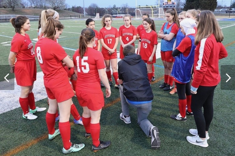 Freshman Lauren Spehlmann (far right, in red warmup jacket) stands with her teammates as the coach addresses the team.