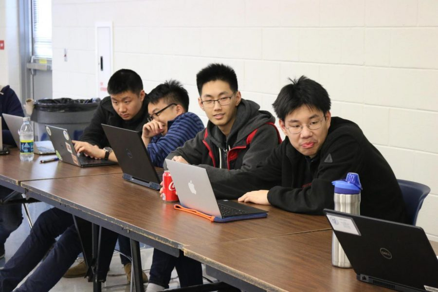 Seniors+Kevin+Wang%2C+Benjamin+Xu%2C+James+Kuang%2C+and+junior+William+Wang+keep+an+eye+on+the+team+standings+as+participants+scramble+to+fill+out+their+answers.