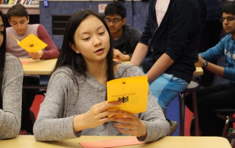 Reading across her menu, a student prepares to order traditional German food.
