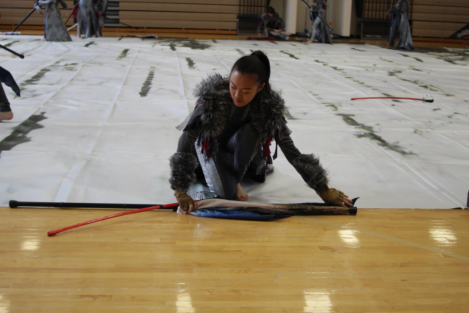 Rolling+out+a+large+painted+mat%2C+sophomore+Suemin+Yang+helps+the+color+guard+prepare+the+gym+floor+for+their+performance.%0A