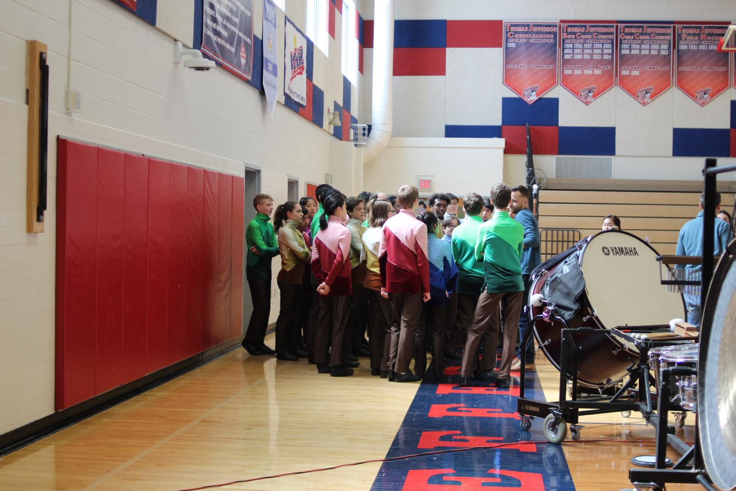 Huddling+up+prior+to+their+performance%2C+the+drumline+receives+a+talk+from+teachers+Adam+Foreman+and+Steve+Ballard.+%0A