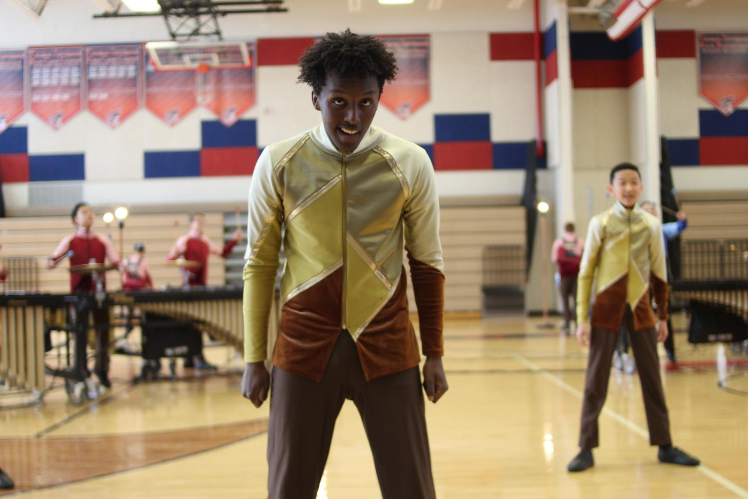 With+percussion+music+playing+in+his+background%2C+freshman+Nathanael+Tewodros+stands+near+the+audience%2C+shoulders+hunched.+Although+the+main+focus+of+the+performance+is+the+music%2C+the+performance+involves+dance+as+well.+%E2%80%9CWhen+we+don%E2%80%99t+use+our+instruments%2C+we+are+typically+doing+choreographed+dances+that+are+made+to+match+musical+phrases+or+little+queues%2C%E2%80%9D+Tewodros+said.%0A