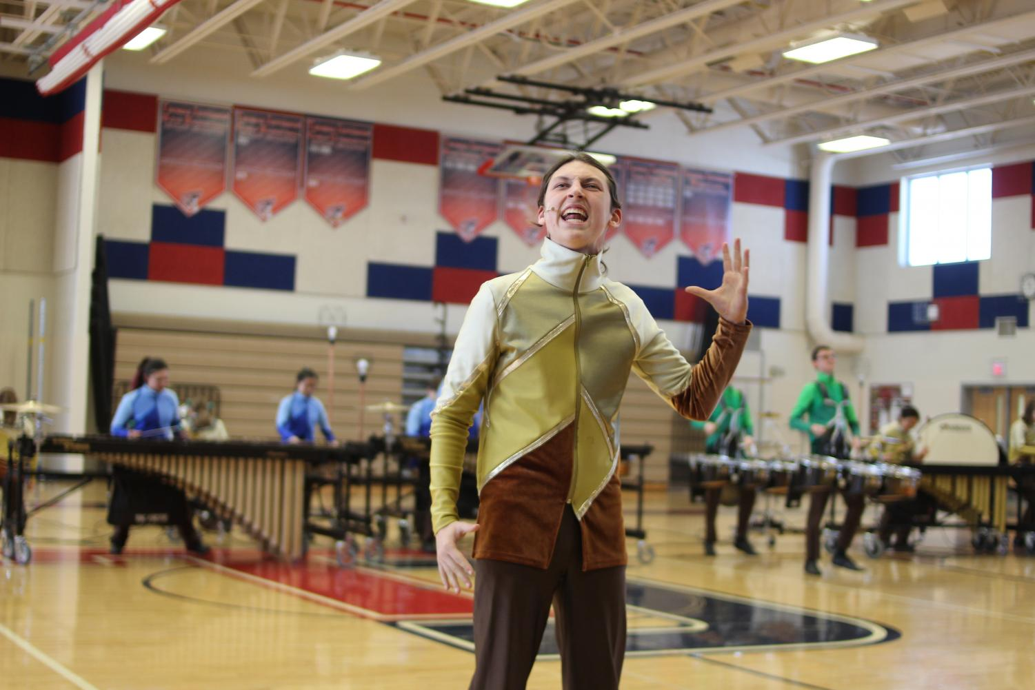 Using+hand+gestures+to+emphasize+his+words%2C+freshman+Zander+Kuebler+provides+a+narrated+introduction+to+the+drumline+performance.+%0A
