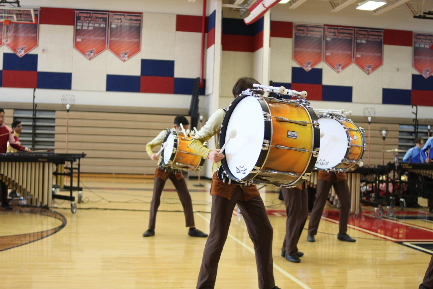 Leaning+into+his+drum%2C+freshman+Benjamin+Chang+plays+the+instrument%2C+complementing+the+other+percussionists+in+the+performance.+%E2%80%9CAt+the+start+of+the+season%2C+I+hadn%E2%80%99t+even+carried+a+bass+drum+before+so+it+was+hard+to+get+started+with+drumline.+But%2C+as+they+say%2C+practice+makes+perfect%2C%E2%80%9D+Chang+said.+%E2%80%9CI+just+kept+trying+to+stay+upright+with+the+drum+throughout+each+rehearsal+and+eventually+carrying+it+became+easy.%E2%80%9D%0A
