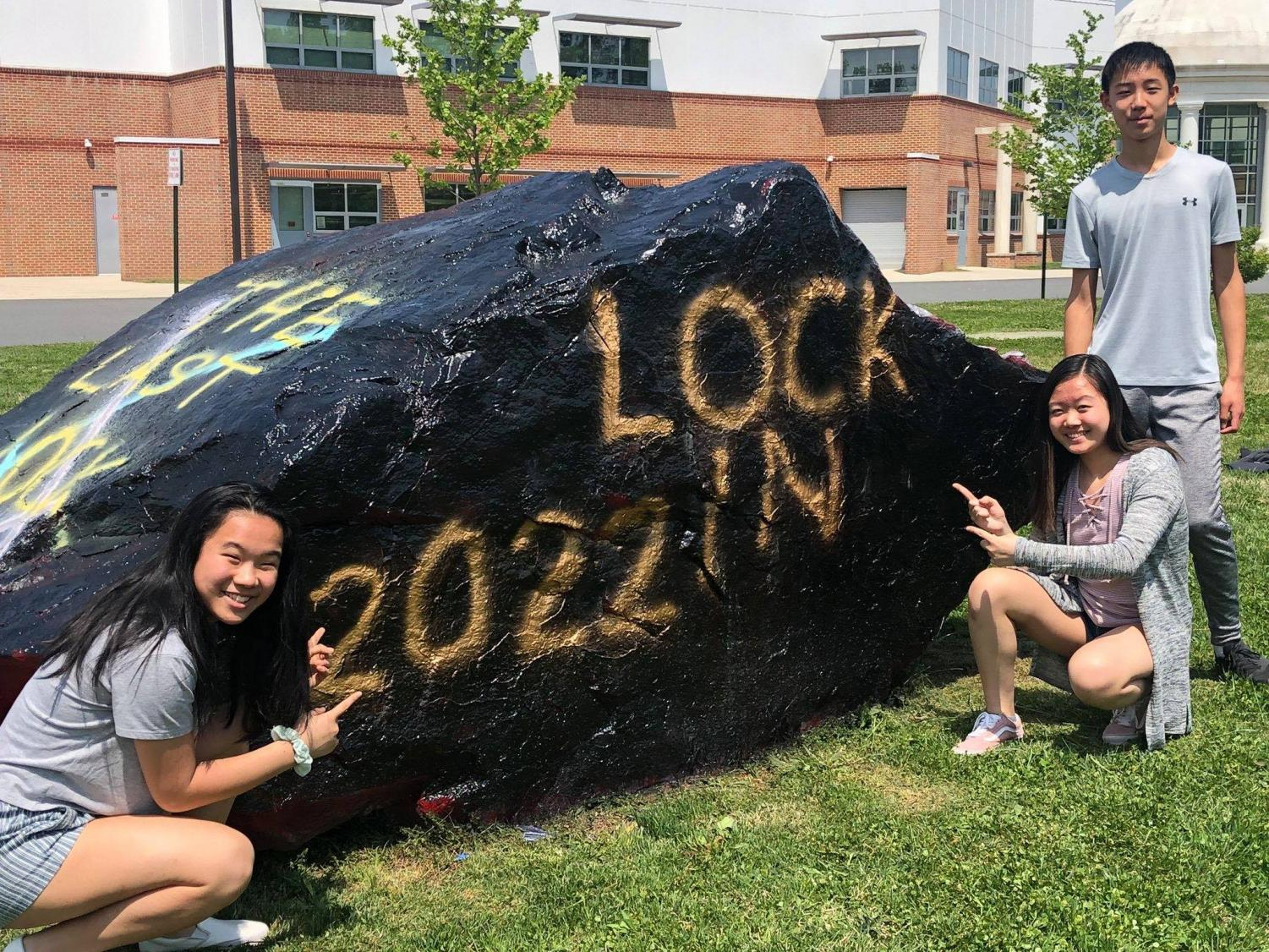 2022 class council members Caroline Chen (far left), Melissa Wu, and Leon Jia stand beside the rock outside Jefferson after they painted it for the lock-in. Even though there will no longer be a freshman lock-in, they're hopeful that a similar event will replace it.