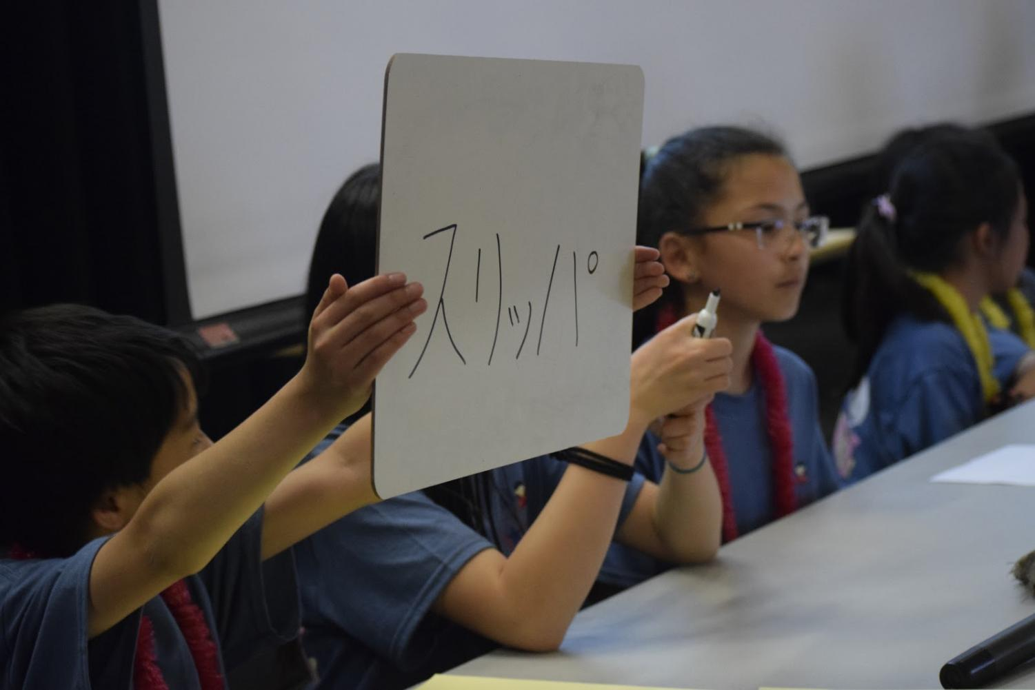 A student competing in the K-4 division's championship round holds up their answer for a toss-up question.
