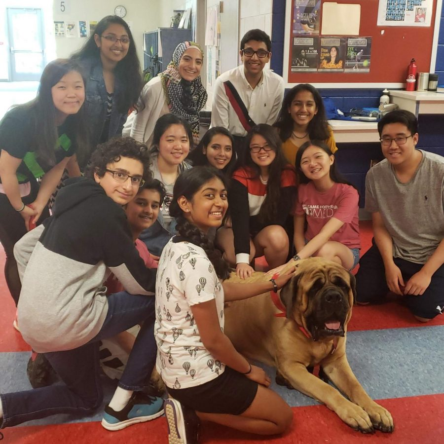 The tjTODAY staff pose with Jackson the therapy dog during one of his classroom visits during Stress Less Laugh More week.