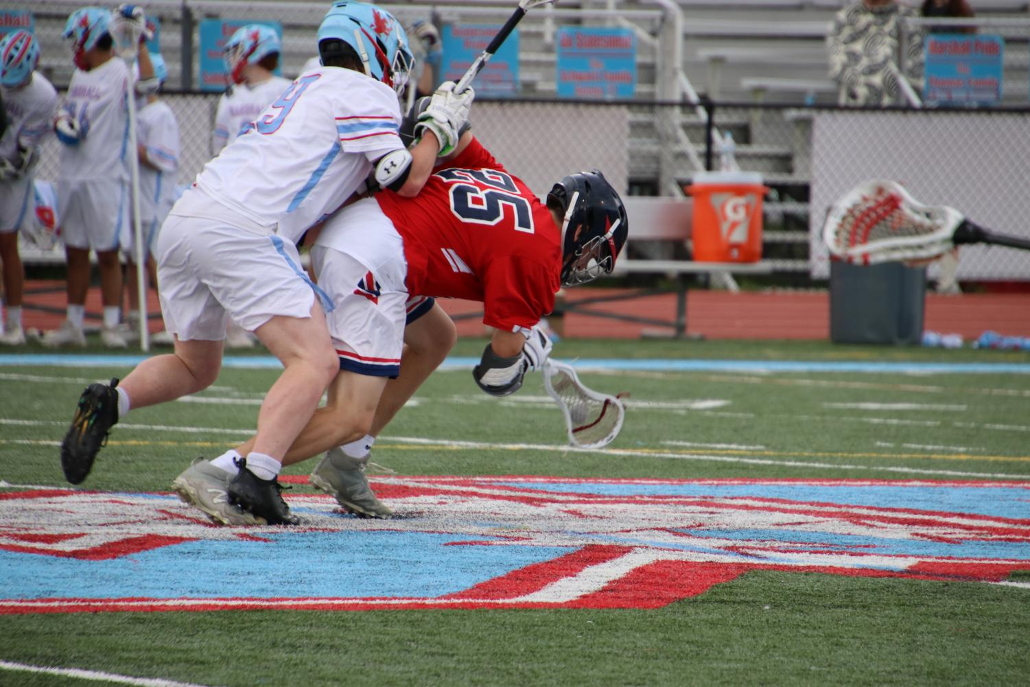 Bending over to dodge an opponent, midfielder Caden Philips battles to maintain possession. The team's efforts ultimately weren't enough as they lost 11-7.