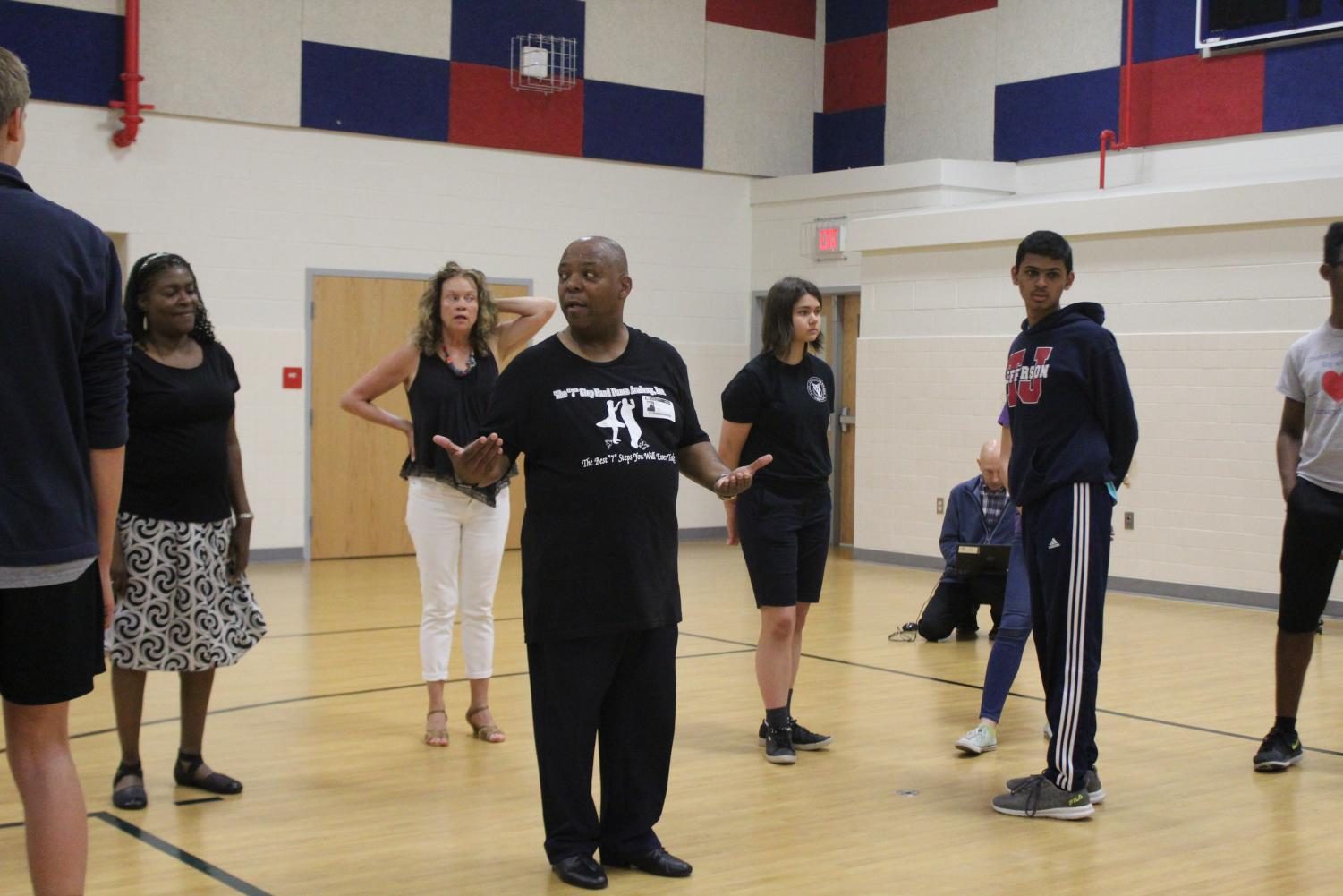 After Señora Gendive asks a question about a particular step, Instructor Morton gathers the attention of the other dancers and they all watch him repeat the step slowly.