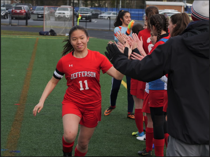 Player+Sherrie+Feng+high-fives+the+team+as+she+gets+ready+to+take+the+field+before+the+game.+Khushie+Matharoo%2C+typically+goalie%2C+stands+in+the+front+of+the+line.