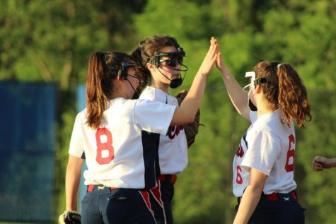 After preventing the runners on third and second from scoring additional runs on a sacrifice bunt attempt in the top of the third inning, sophomore Alexandra Friedman (right), senior Grace Stewart (middle), and freshman Michelle Boisvert (left) celebrate with a high-five before returning to their respective positions.