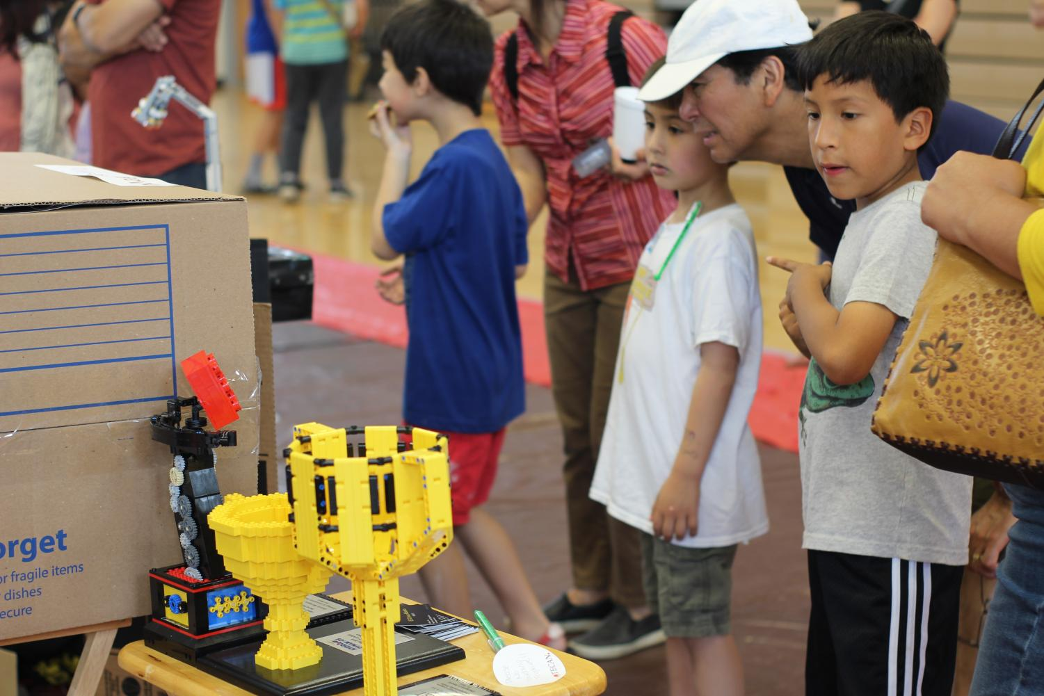 A+father+and+his+children%2C+both+in+elementary+school+observe+the+contraptions+built+by+the+multiple+FTC+%28First+Technology+Challenge%29+teams+present+at+Techstrav+2019.