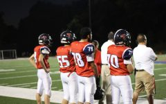 Standing on the sideline, a group of players intensely watch the game