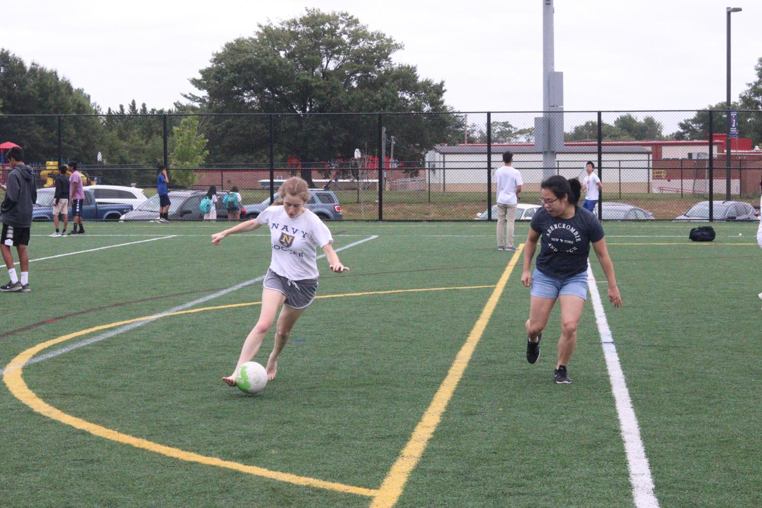 Shea Weingold kicks a soccer ball and Jenny Li waits for the ball to come her way. Students played soccer, volleyball, and tug of war during the Bash. Spending fun time with friends after a stressful week is one of the largest reasons students decided to attend the Bash.