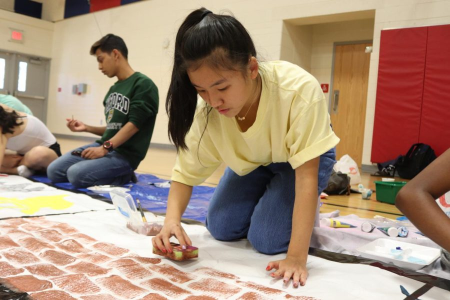 Junior Tammy Ding uses a sponge to paint bricks in the middle of 2021's banner. 2021's banner was a representation of various items on a filmstrip.