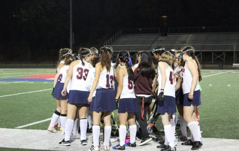 At the end of a timeout, the team huddles and cheers by assembling their field hockey sticks together in the center of the circle.