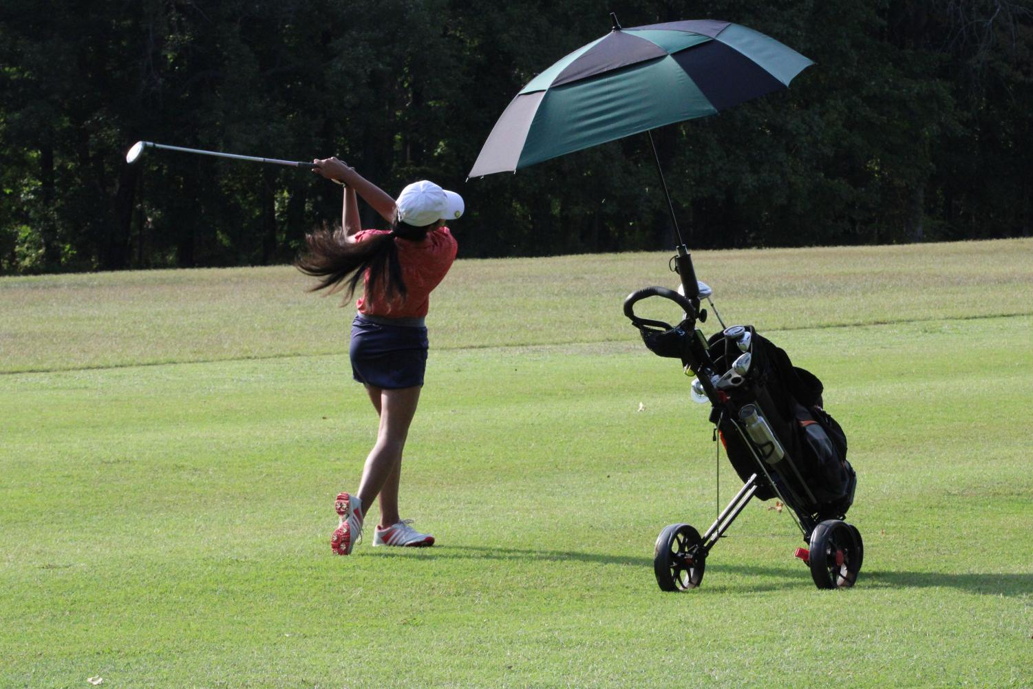 Senior Khushi Chawla swings her golf club, sending her ball flying on the green. To prepare for regionals, Chawla practiced twice on the course where regionals would be held (Laurel Hill Golf Club).