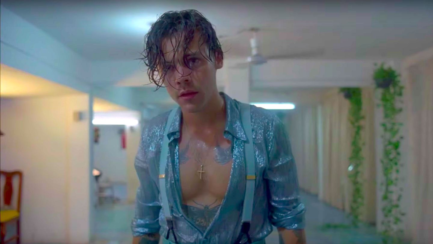Image courtesy of MTV. Dressed in pastel blue, Styles stares blankly into the distance, entirely drenched under swaying, flickering lights, in the