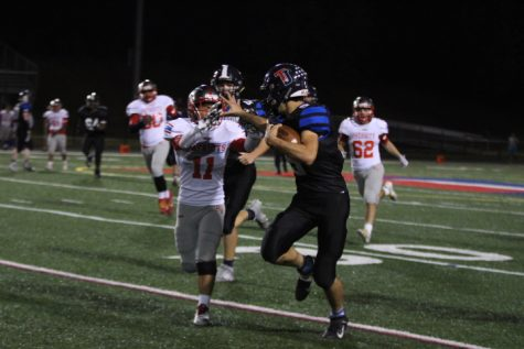Stiff arming a defender, running back Niko Economos (5) charges towards the end-zone