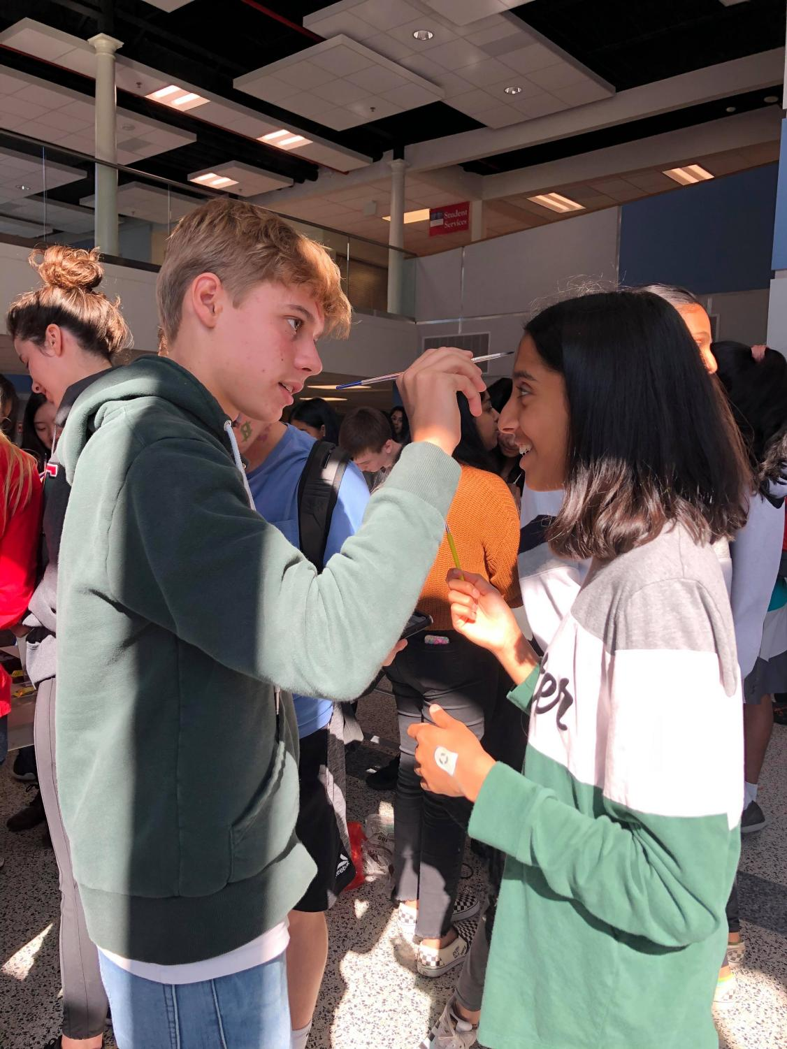 Freshman Jean Lavigne Du Cadet paints freshman Nirja Divekar's face during NAHS's face painting event in Nobel Commons during JLC.