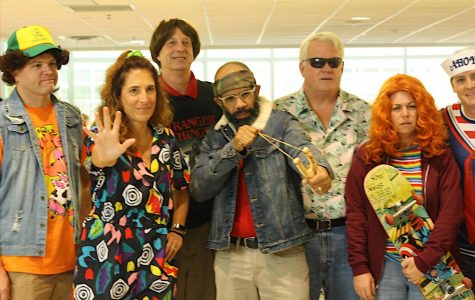 Posing for a picture after having finished conducting the Halloween contest, teachers, from left to right, Mr. Kosatka, Dr. Bonitatibus, Mr. Yohe, Mr. Frank, Mr. Hodges, Ms. Hawkins, and Mr. Resquin, are dressed up as the Stranger Things cast. Representing the characters with their funky patterned 90s clothing, they strike adolescent-like poses.