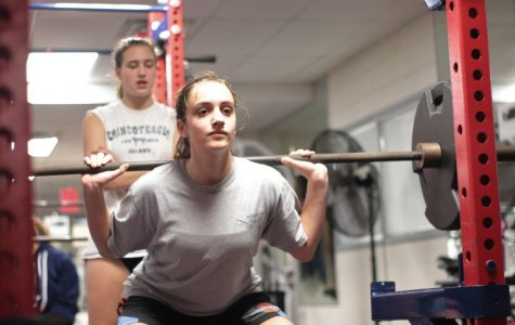 "Junior Sarabeth Joyner lifts a dumbbell in the Jefferson weight room while sophomore Alexandra Fall spots and encourages her. The basketball players are mid-conditioning, where they exercise to build muscle and stamina. ""Conditioning days [are] fun because you're sore the day after and it feels really good,"" freshman Aditi Shukla said."