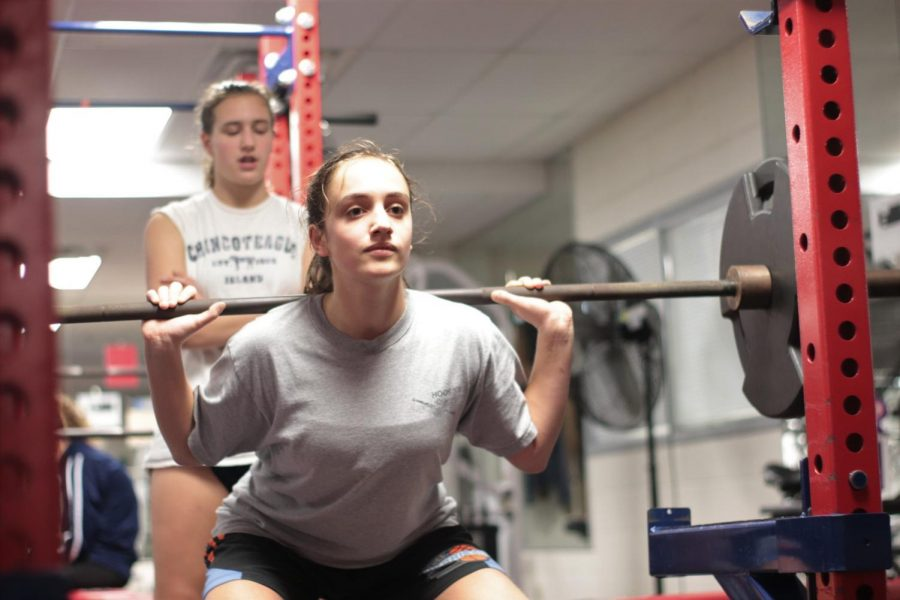 Junior+Sarabeth+Joyner+lifts+a+dumbbell+in+the+Jefferson+weight+room+while+sophomore+Alexandra+Fall+spots+and+encourages+her.+The+basketball+players+are+mid-conditioning%2C+where+they+exercise+to+build+muscle+and+stamina.+%E2%80%9CConditioning+days+%5Bare%5D+fun+because+you%27re+sore+the+day+after+and+it+feels+really+good%2C%E2%80%9D+freshman+Aditi+Shukla+said.+%0A