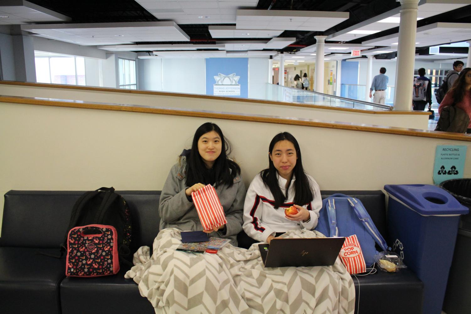 """Eating popcorn and getting ready to make thank you cards, seniors Crystal Shi and Arwen Chandler sit on one of the couches in the Franklin Commons. """"It's a chance to relax just before break,"""" Chandler said."""