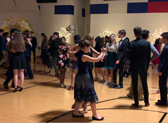 Students waltz to live music performed by the symphonic orchestra at the Viennese Ball. The event lasted three hours, and was filled with music and dancing. Decorations lining the sides of the scene were set up by orchestra students and parent volunteers.