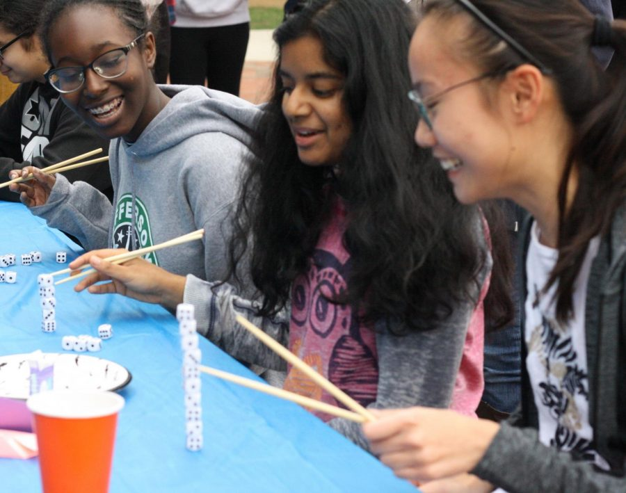 "Sophomores Abena Kyereme-tuah (far left), Tanisha Pagadala and Natalie Wu laugh as the use chopsticks to stack dice on top of each other. ""For me, it was nice that we were all able to go to the same eighth period and hang out and have fun,"" Tanisha Pagadala said."