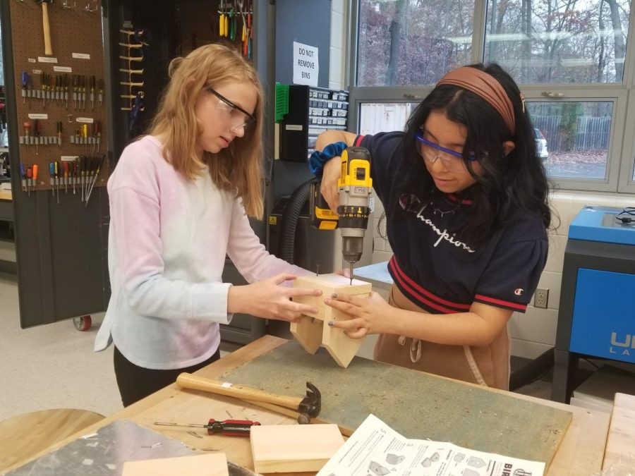 """Freshman Alyssa Gatesman (left) holds the birdhouse steady as freshman Mary Loyola-Gomez (right) uses a drill to assemble the parts. """"The birdhouse activity was really fun since we got to make it on our own. My favorite part was hammering it together,"""" Gatesman said. """"I think the birdhouse activity should be continued because it encourages students to build for fun and do an activity aside from schoolwork."""""""