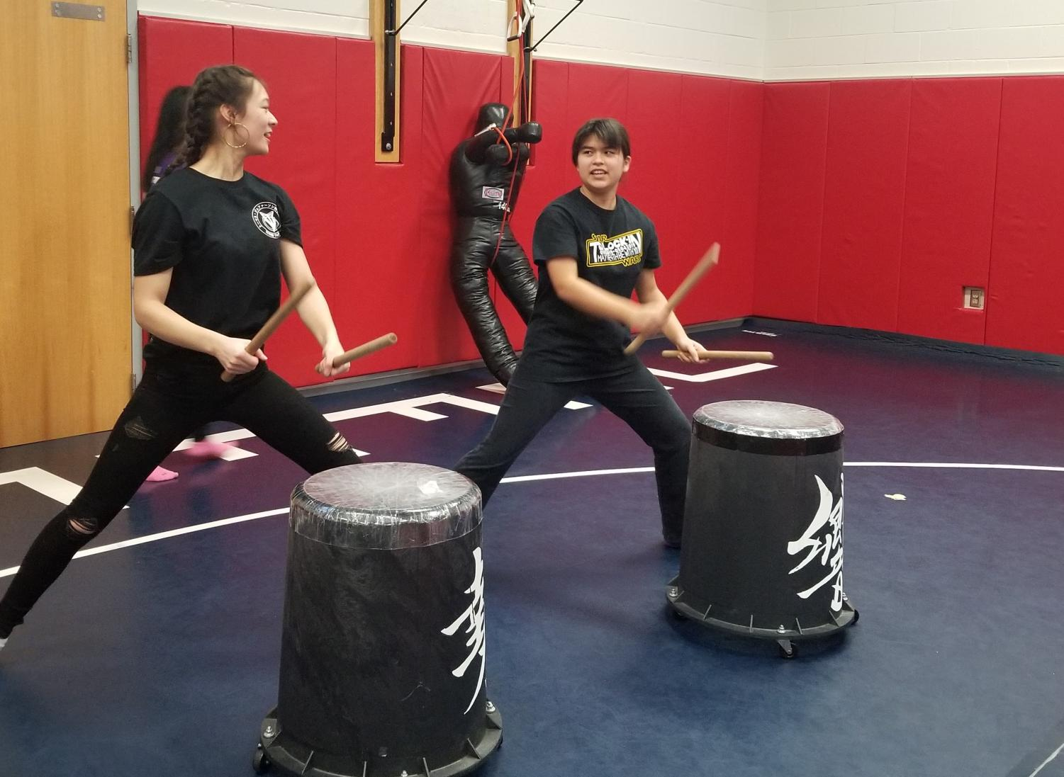 """Sophomores Alyssa Rask (right) and Alana Nii (left) perform a taiko routine as a duet. """"I love the program here at TJ because it's very relaxed. I also do taiko outside of school, and my experience with the taiko community is just - there's a lot of fantastic people,"""" Nii said."""