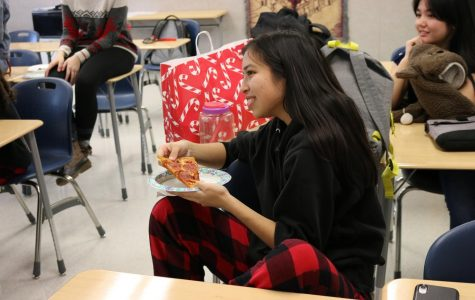Wearing pajamas to celebrate Friday's Festive and Flannel Friday, junior Hailey Nguyen smiles and prepares to take a bite of her pizza.