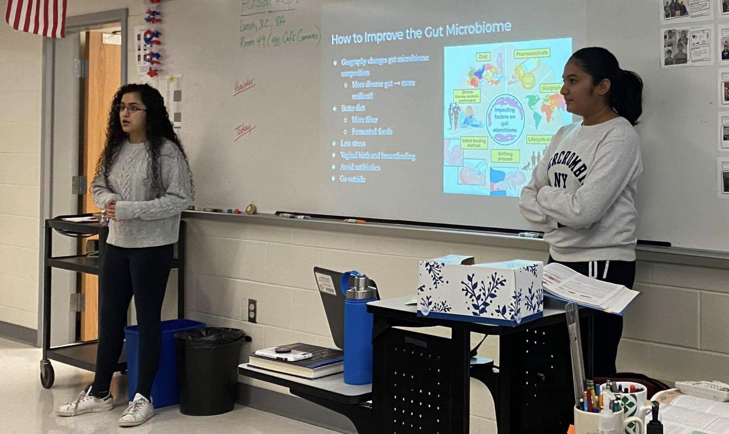 """Juniors Gurleen Kaur and Neha Sripathi present about the gut microbiome at a club meeting. The gut microbiome is one of many specific aspects of microbiology that the officers hope to explore in depth. """"The gut microbiome is something that's really interesting, [such as] how it impacts your physical and your mental health,"""" Kaur said."""