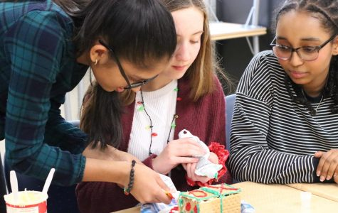 "Freshmen Richa Gupta (left), Vivian Denny (center), and Maya Makonnen (right) build a gingerbread house together. ""This was a fun stress-reliever before winter break,"" Makonnen said."