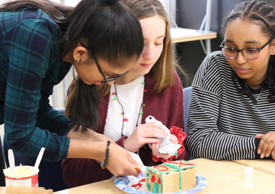 Freshmen+Richa+Gupta+%28left%29%2C+Vivian+Denny+%28center%29%2C+and+Maya+Makonnen+%28right%29+build+a+gingerbread+house+together.+%E2%80%9CThis+was+a+fun+stress-reliever+before+winter+break%2C%E2%80%9D+Makonnen+said.+