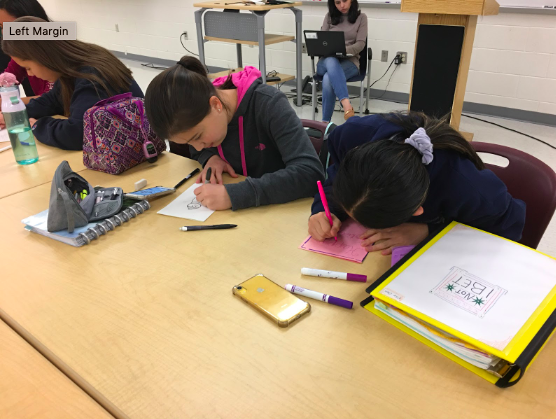 "Freshman Jessica May and Ellie Chung work together to decorate the holiday cards. ""I think it's a really good opportunity and it's really nice to be able to make cards for these kids in the hospitals during Christmas,"" May said."