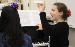 Reading from sheet music, sophomore Micaela Wells vocalizes with other members of Jefferson's Madrigals group