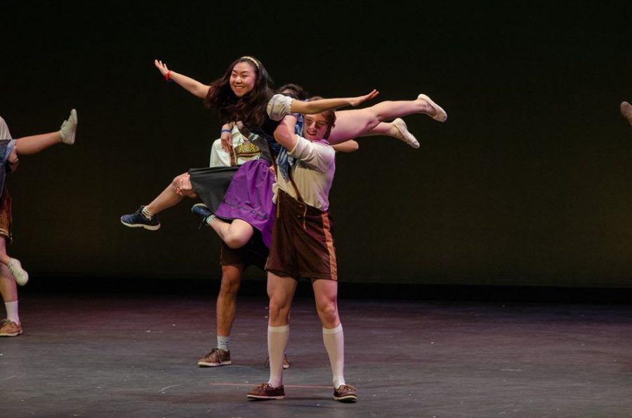 Arms held out, graduated senior Tiffany Zhang is twirled into the air.