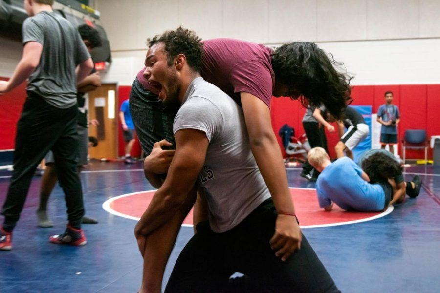 Roaring triumphantly, senior Caleb O'Cain suplexes freshman Rushil Umaretiya during a wrestling practice.