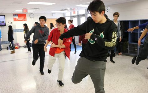 In unision with two other students, senior Jae Canneti practices a move from Urban Dance Movement's iNite act