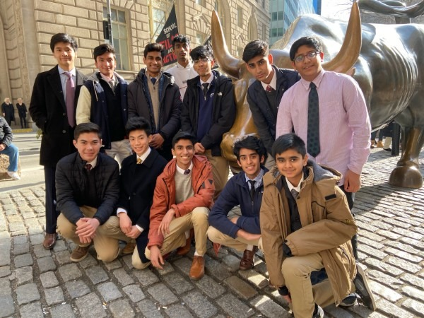 The investment club members pose in front of the Charging Bull statue near Wall Street. The bull has captured tourists' imagination, Business Insider said. The 7100-pound statue is said to symbolize brazen optimism among investors.