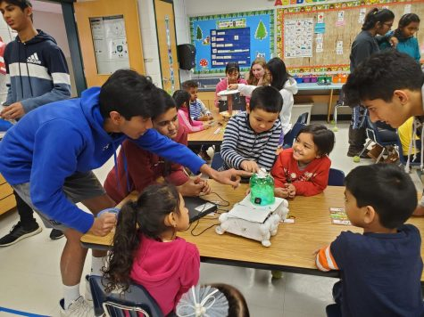 Freshman Rusheel Nadipally and freshman Dhruv Khatod demonstrate circuits and electrical components to eager elementary school students.
